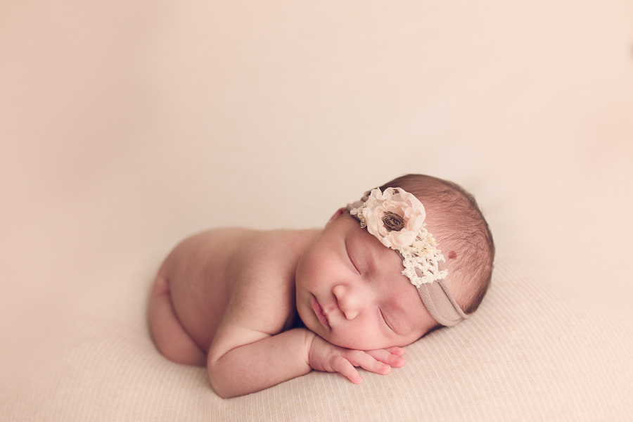 san ramon newborn photographer with new baby girl in flower hand band
