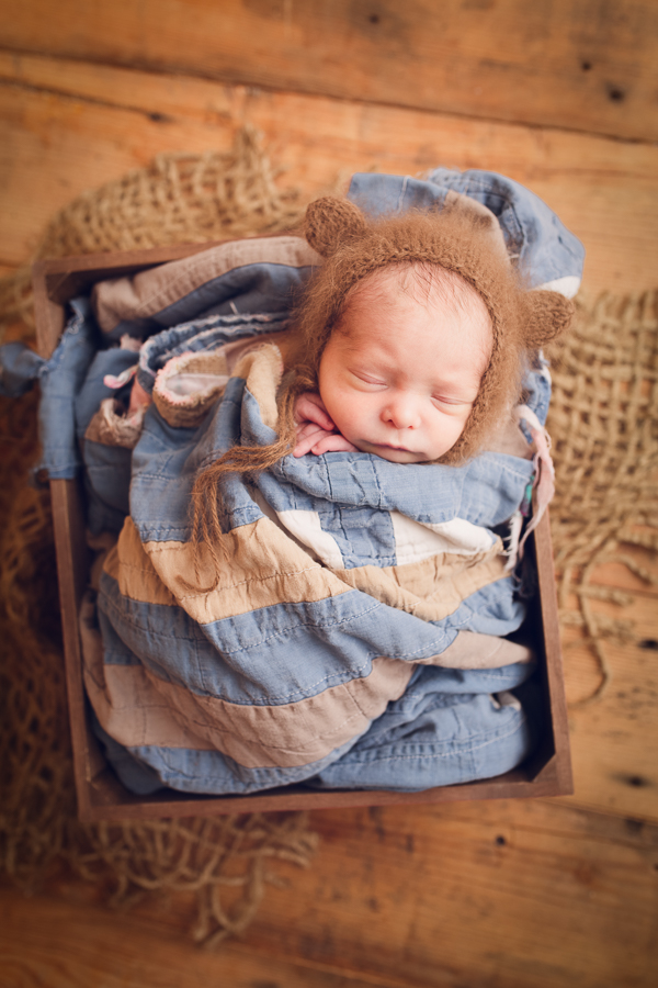 Baby Photographer Livermore baby boy cradled in a quilt and bear hat